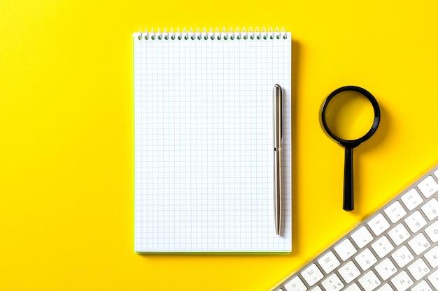 Het witte open kladblok en computertoetsenbord geïsoleerd op geel