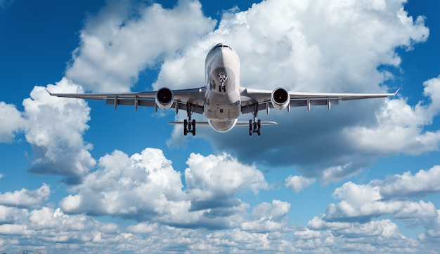 Het witte passagiersvliegtuig vliegt in de blauwe hemel met wolken