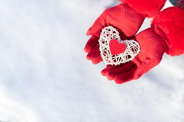 Het witte rotanhart met kleine rode in het midden in vrouw dient rode handschoenen op sneeuw in.