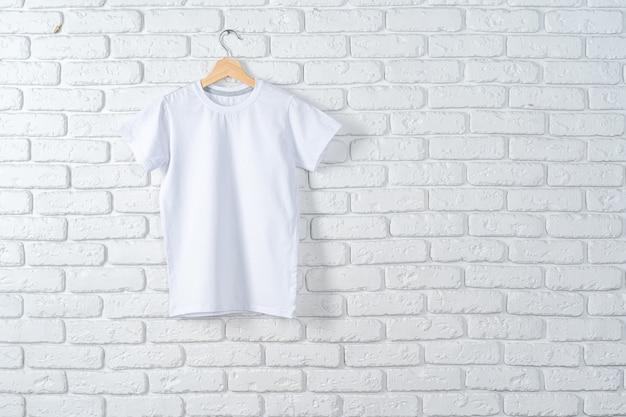 Het witte t-shirt hangen op hanger tegen bakstenen muur, exemplaarruimte