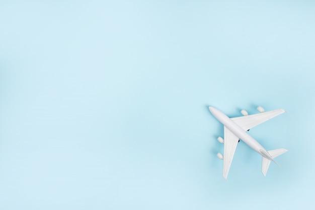 Het witte vliegtuigmodel op een blauwe achtergrond. reizen .