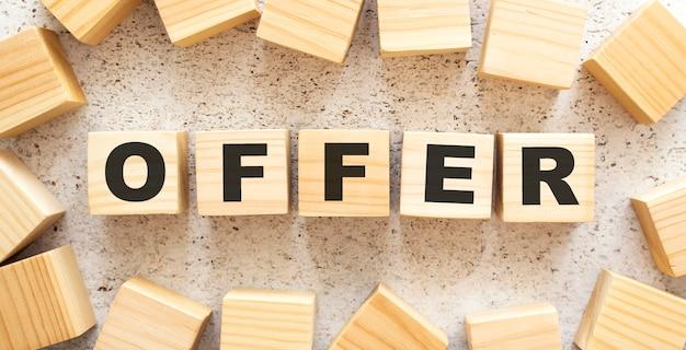 Het woord aanbieding bestaat uit houten kubussen met letters, bovenaanzicht op een lichte achtergrond.