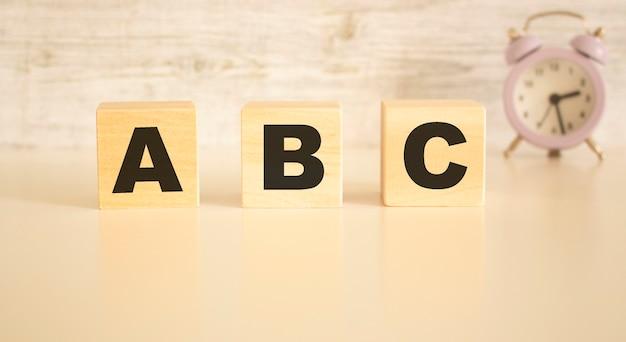 Het woord abc bestaat uit houten blokjes met letters, bovenaanzicht op een lichte achtergrond.
