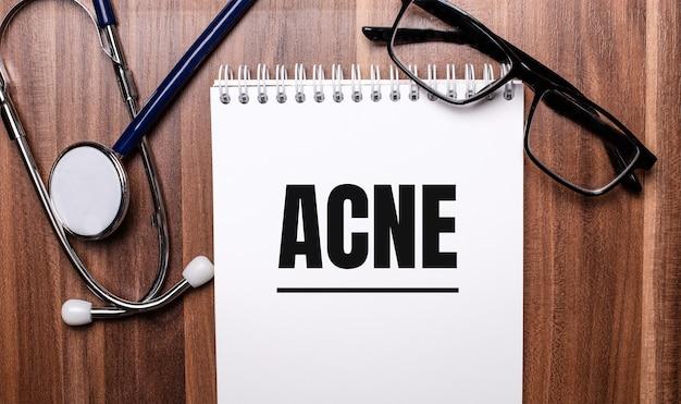 Het woord acne is geschreven op wit papier op een houten oppervlak naast een stethoscoop en een bril met een zwart montuur