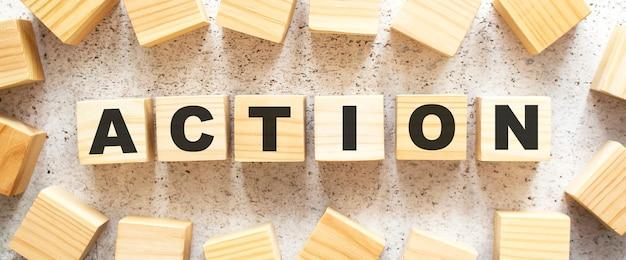 Het woord actie bestaat uit houten kubussen met letters, bovenaanzicht op een lichte ondergrond.