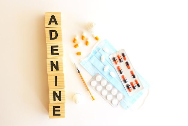 Het woord adenine is gemaakt van houten kubussen op wit