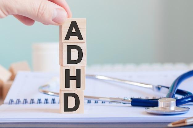 Het woord adhd is geschreven op houten kubussen in de buurt van een stethoscoop op tafel medisch concept