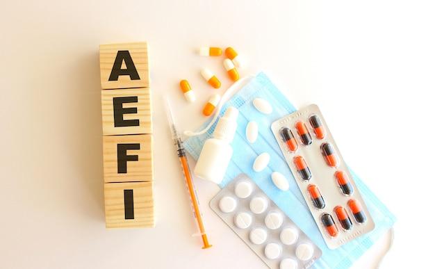 Het woord aefi is gemaakt van houten kubussen op een witte achtergrond.