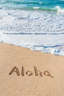 Het woord aloha geschreven in het zand op het strand met een golf wassen binnen