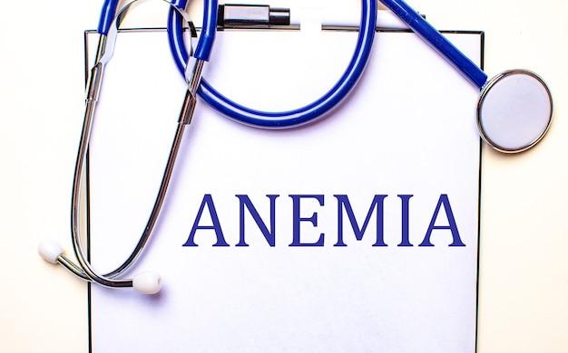 Het woord anemia is geschreven op een wit vel naast de stethoscoop. medisch concept