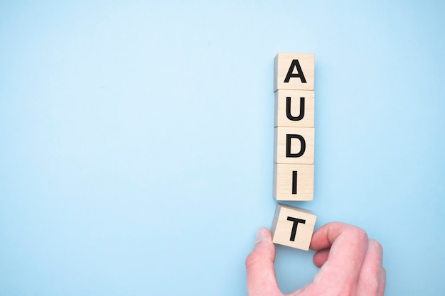 Het woord audit verschijnt houten kubussen. onderwijs concept
