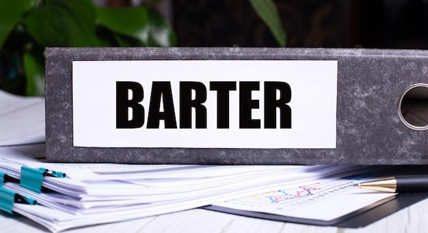 Het woord barter is geschreven op een grijze map naast documenten. bedrijfsconcept