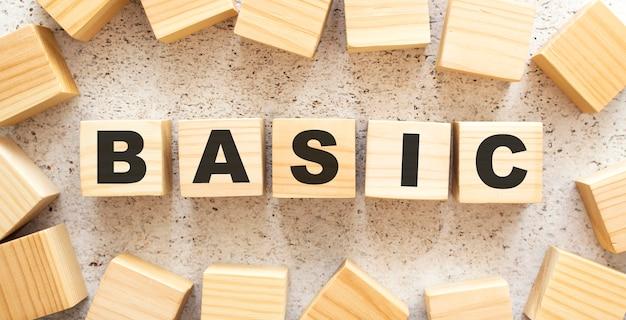 Het woord basic bestaat uit houten kubussen met letters, bovenaanzicht op een lichte achtergrond. werkruimte.
