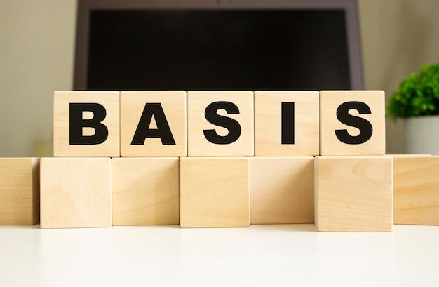 Het woord basis is geschreven op houten kubussen die op de kantoortafel voor een laptop liggen.