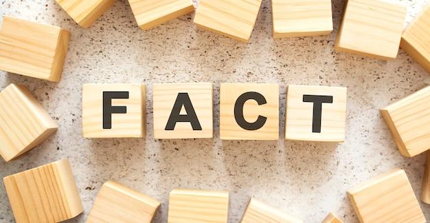 Het woord bestaat uit houten blokjes met letters, bovenaanzicht op een lichte achtergrond. werkruimte.