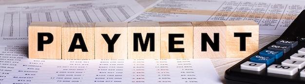 Het woord betaling is geschreven op houten kubussen in de buurt van de grafieken en rekenmachine.
