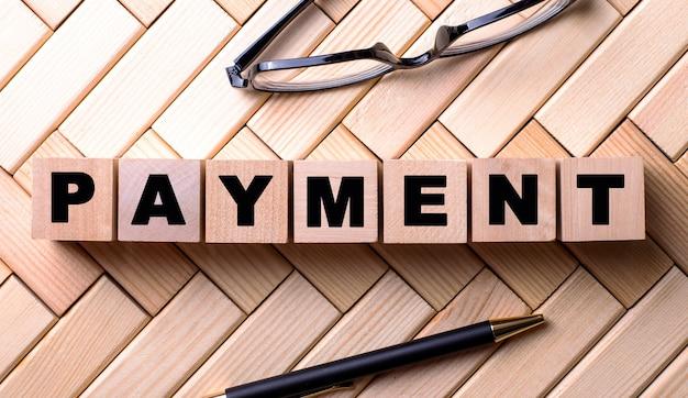 Het woord betaling wordt geschreven op houten kubussen op een houten oppervlak naast een pen en een bril