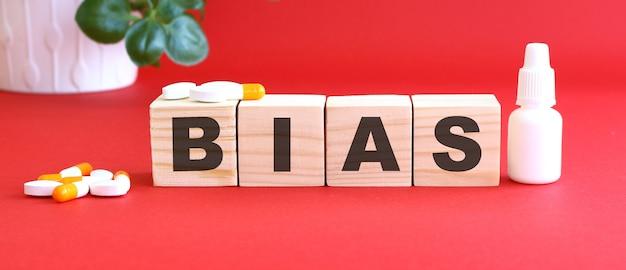 Het woord bias is gemaakt van houten kubussen op een rode achtergrond met medicijnen.