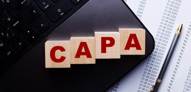 Het woord capa is geschreven op houten blokjes op het toetsenbord naast de pen