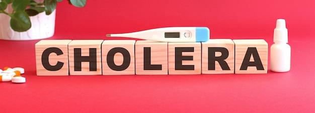 Het woord cholera is gemaakt van houten blokjes op een rood oppervlak met medicijnen