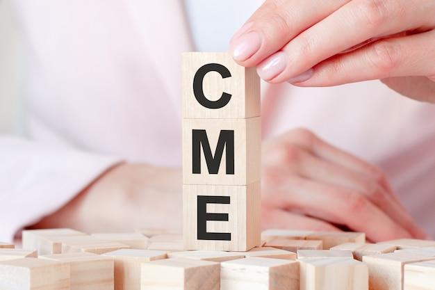 Het woord cme op houten stuk speelgoed blokken met dameshanden, roze oppervlakte