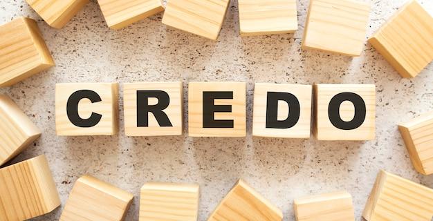 Het woord credo bestaat uit houten kubussen met letters, bovenaanzicht op een lichte achtergrond. werkruimte.