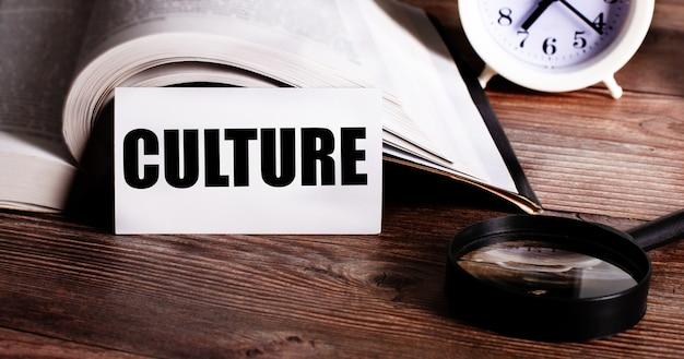 Het woord cultuur geschreven op een witte kaart in de buurt van een open boek, een wekker en een vergrootglas