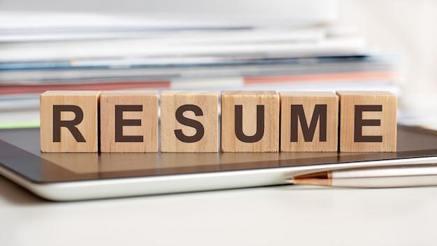 Het woord cv is geschreven op houten kubussen die op een notitieblok staan, in het oppervlak een stapel documenten