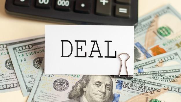 Het woord deal is geschreven op de witte kaart. kaart aan de muur met 100 dollarbiljetten en een rekenmachine