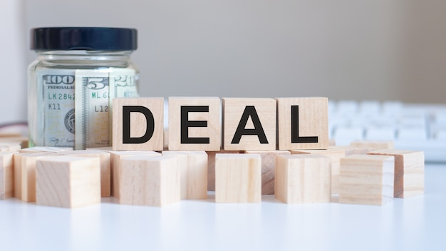 Het woord deal op de houten blokken en een bank met geld in de tafel, bedrijfsconcept