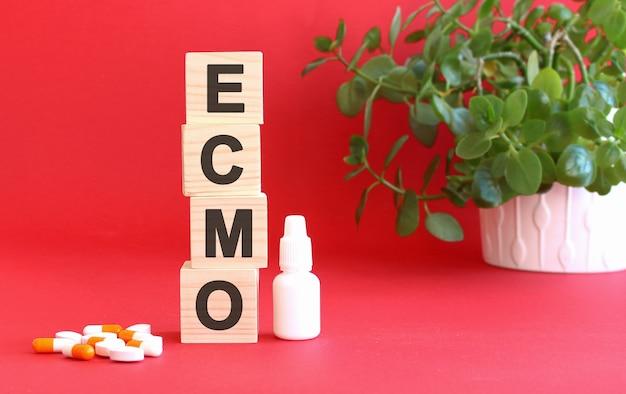 Het woord ecmo is gemaakt van houten blokjes op een rood oppervlak met medicijnen.