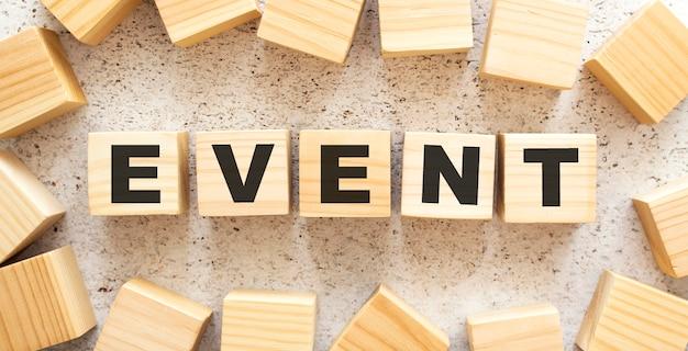 Het woord event bestaat uit houten kubussen met letters, bovenaanzicht op een lichte achtergrond.