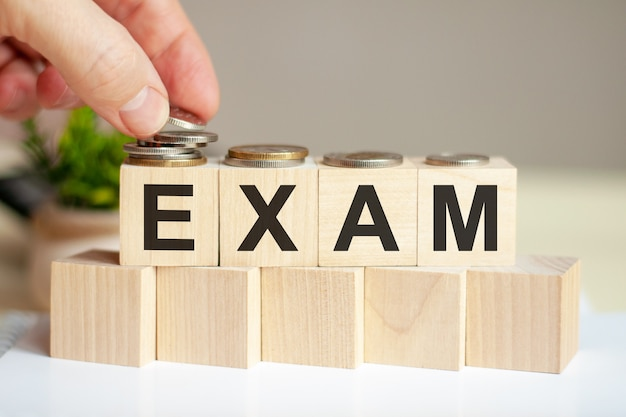 Het woord examen geschreven op houten kubussen. de hand van een man plaatst de munten op het oppervlak van de kubus. groene potplant op de achtergrond. zakelijk en financieel concept