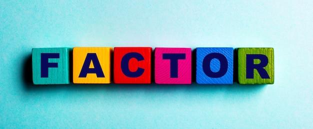 Het woord factor is geschreven op veelkleurige heldere houten kubussen op een lichtblauwe tafel