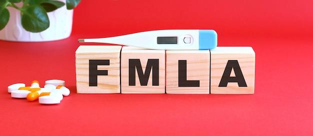 Het woord fmla is gemaakt van houten blokjes op een rood oppervlak met medicijnen.