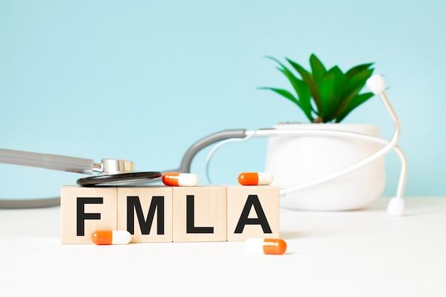 Het woord fmla is geschreven op houten kubussen in de buurt van een stethoscoop op een houten achtergrond. medisch concept