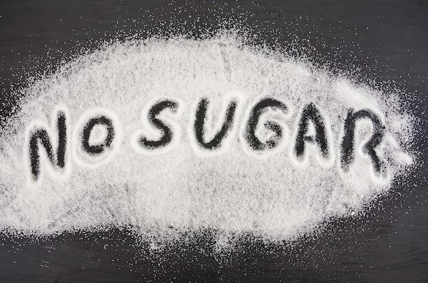 Het woord geen suiker is geschreven in witte kristalsuiker. suiker schade concept.
