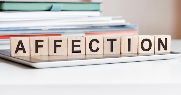 Het woord genegenheid is geschreven op houten kubussen die op een notitieblok staan, op de achtergrond een stapel documenten, selectieve focus. kan worden gebruikt voor zaken, onderwijs, financieel concept