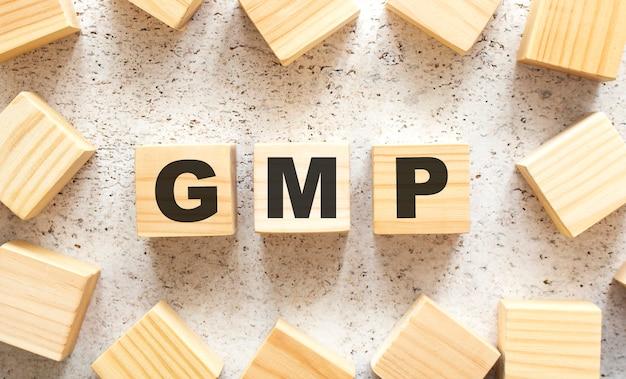 Het woord gmp bestaat uit houten blokjes met letters