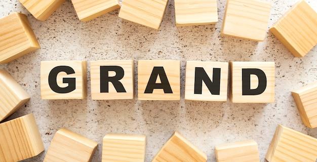 Het woord grand bestaat uit houten kubussen met letters, bovenaanzicht op een lichte achtergrond. werkruimte.