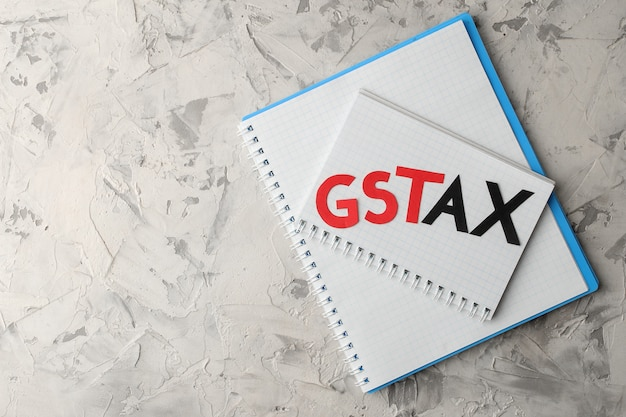 Het woord gst tax met een notitieblok op een lichte betonnen achtergrond. bovenaanzicht met ruimte voor tekst
