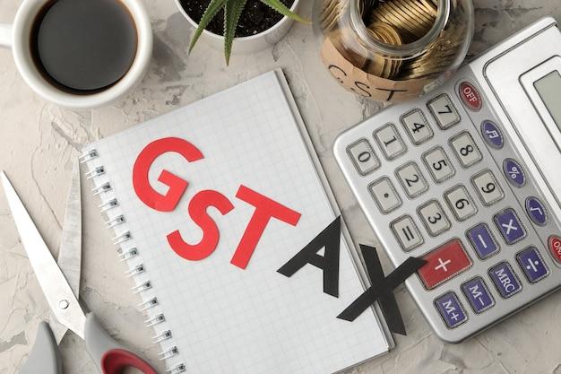 Het woord gst tax met een notitieblok, rekenmachine en munten in een bank op een lichte betonnen achtergrond. uitzicht van boven