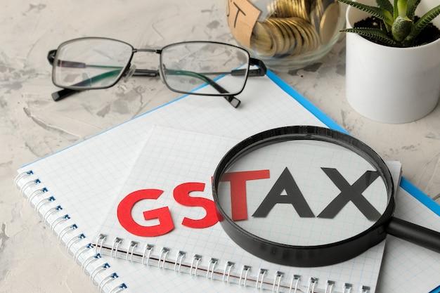 Het woord gst tax onder een vergrootglas met een notitieboekje, bril, pen en munten in een bank op een lichte betonnen achtergrond.