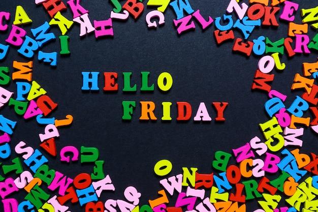 Het woord hello friday uit veelkleurige houten letters op een zwarte achtergrond