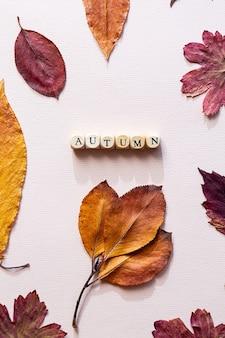 Het woord herfst gemaakt van houten kubussen op een roze tafel met gekleurde herfstbladeren