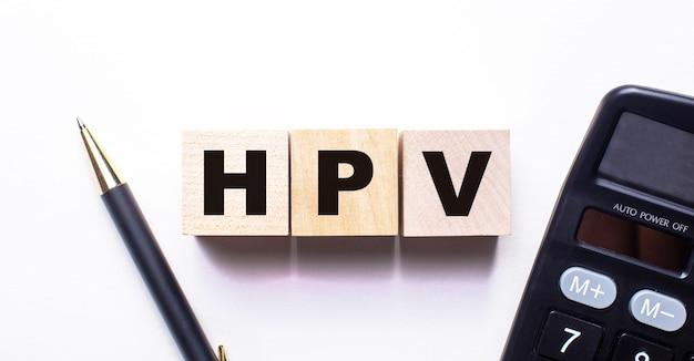 Het woord hpv is geschreven op houten blokjes tussen een pen en een rekenmachine op een lichte ondergrond