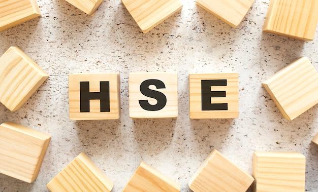 Het woord hse bestaat uit houten kubussen met letters, bovenaanzicht op een lichte achtergrond. werkruimte.