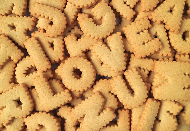 Het woord i love u wordt gespeld met koekjes in de vorm van een alfabet op de stapel dezelfde koekjes