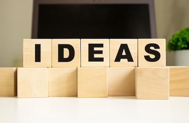 Het woord ideen is geschreven op houten kubussen die op de kantoortafel voor een laptop liggen. bedrijfsconcept.