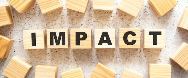 Het woord impact bestaat uit houten kubussen met letters, bovenaanzicht op een lichte achtergrond. werkruimte.